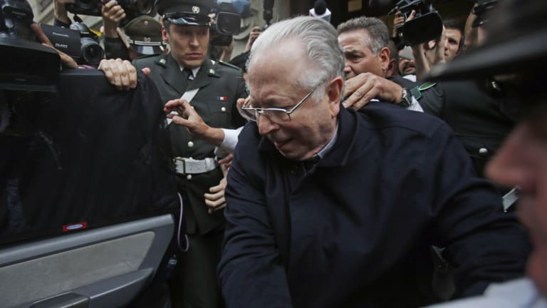 Fernando Karadima is escorted from a court after testifying in a case that three of his victims brought against the Catholic Church in Santiago, Chile, in 2015.