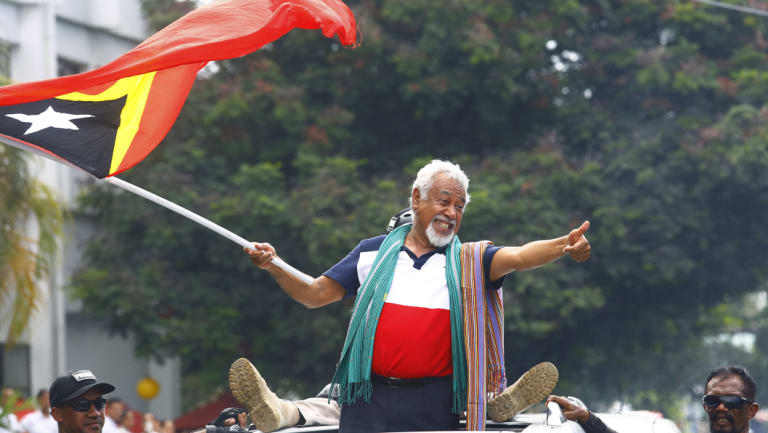 East Timorese independence hero Xanana Gusmao waves a national flag at a pre-election rally.