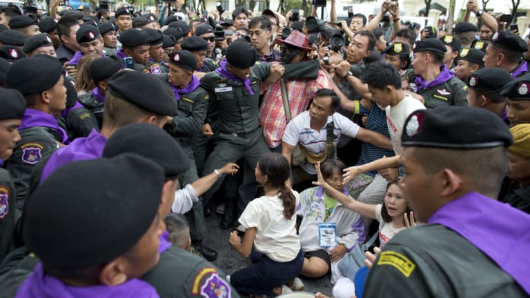 Thai police officers scuffle with pro-democracy supporters and journalist and surround pro-democracy leaders Nuttaa Mahattana, seated with her hands, raised on Tuesday.