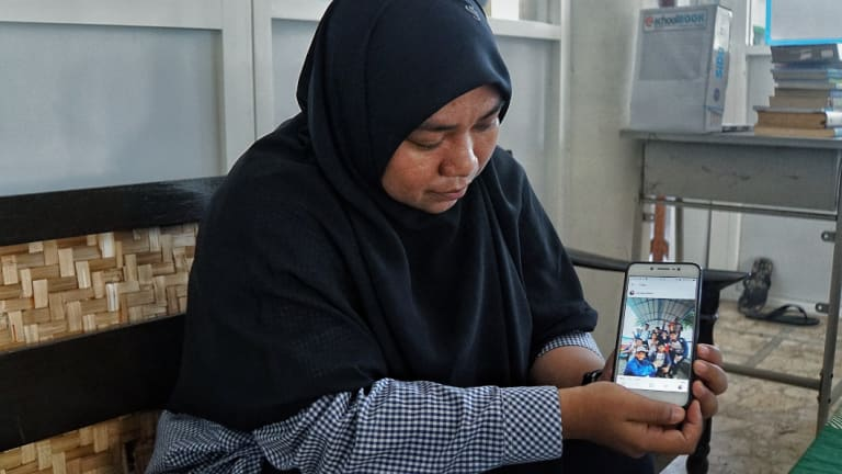 Hafidatur Romlah, who taught some of Dita Oeprianto's children, shows a picture of one of them on a school field trip.