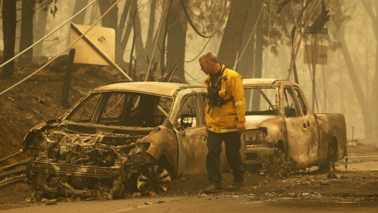 A Sonoma Valley firefighter inspects burned out cars to check for human remains.