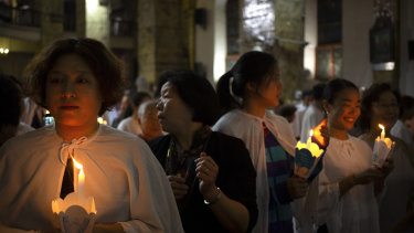 Members of the faithful hold candles during a mass at the Cathedral of the Immaculate Conception, a government-sanctioned Catholic church in Beijing.