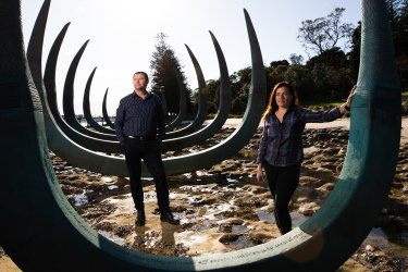 Alison Page and Dillon Kombumerri with sculpture 'The Eyes of the Land and Sea' at Captain Cook's landing place in Kamay Botany National Park.