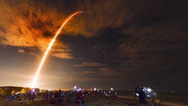 Crowds on the beach in Cape Canaveral, Florida watch the launch of the SpaceX Falcon 9 Crew Dragon on its Crew-1 mission carrying four astronauts, Sunday, November 15.