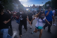 Defying a ban on gatherings imposed due to the COVID-19 outbreak, protesters run from tear gas fired by riot police in Bangkok on Sunday.