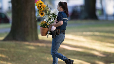 New Zealand police carry flowers left by well wishers to the Al Noor Mosque.