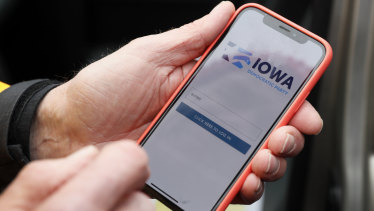 Precinct captain Carl Voss, of Des Moines, Iowa, holds his iPhone that shows the Iowa Democratic Party's caucus reporting app in Des Moines, Iowa.