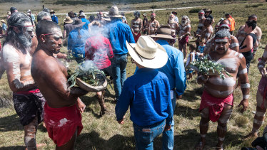 Pro-brumby activists go through the smoke at the ceremony, held on March 6.