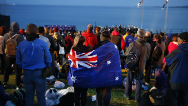 A pair draped with an Australian flag, participate in the Dawn Service ceremony at the Anzac Cove beach in Gallipoli, Turkey.