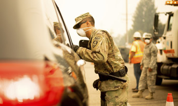 A National Guard specialist from the US Army speaks to a driver at a checkpoint as the Carr fire burns in nearby Redding, California on Saturday.