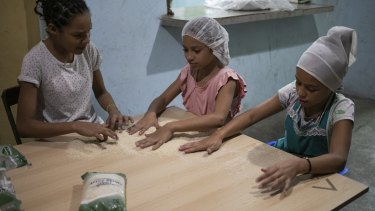 Arbeilis, 11, from left, Cardeilis Torrres, 10, and Camila Grateron, 10, clean rice infested with bugs before cooking it, at a soup kitchen in the Petare slum, in Caracas.
