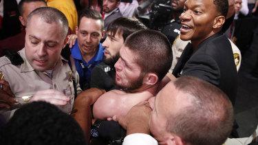 Khabib Nurmagomedov is held back after entering the crowd after defeating Conor McGregor.