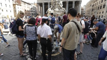 A city police officer watches over as a man refills a bottle with water in front of the Pantheon, in Rome.