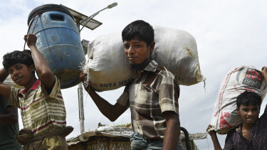 Men carry goods through Kutupalong Camp in Cox's Bazaar, Bangladesh, home to some 900,000 Rohingya refugees.