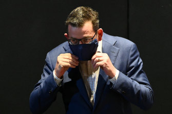 Victorian Premier Daniel Andrews puts on a face mask after fronting the media on Monday.