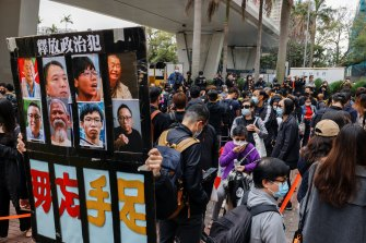 A supporter holds a sign with photos of pro-democracy activists charged under the new national security law in Hong Kong on Monday.