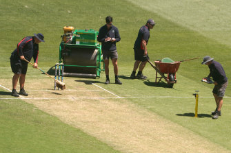 Ground staff inspected the pitch after play on Saturday.