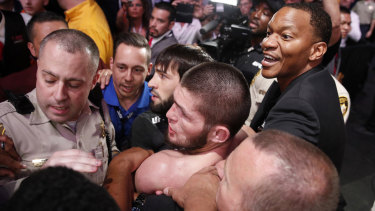 Khabib (bottom centre) is surrounded by police and security after the fight.