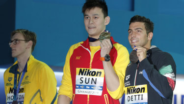 China's Sun Yang, centre, holds up his gold medal with silver medallist Australia's Mack Horton, left.