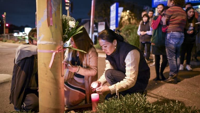 Aivy Nguyen's grieving family light candles.