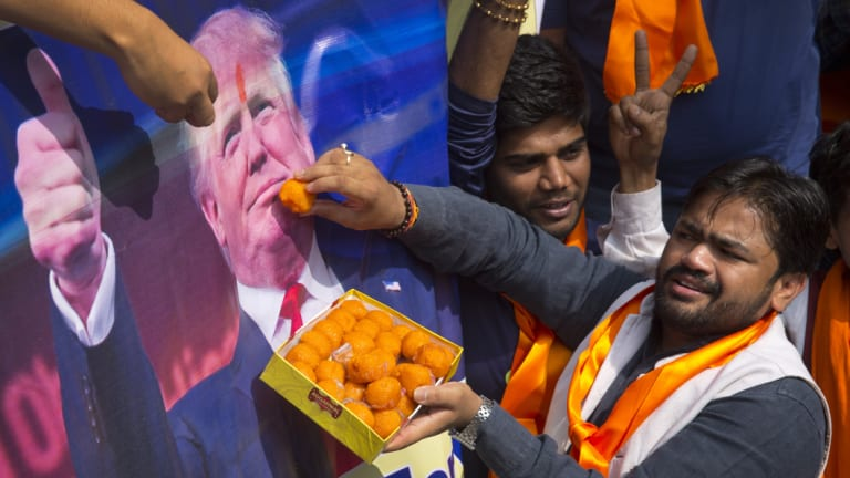 Vishnu Gupta, founder of Hindu Sena, offers sweets to a poster of Donald Trump in 2016.