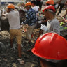 Rescuers try to remove the rubble at the site of a collapsed building in Preah Sihanouk province, Cambodia.