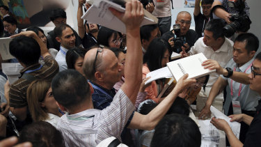 Reporters scramble to get copies of China's national defence white paper before a press conference at the State Council Information Office in Beijing on Wednesday.