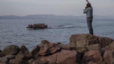 Asylum seekers aboard an overcrowded dinghy cross the Aegean Sea, from Turkey to Lesbos in 2015.