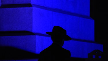 The silhouette of a slouch hat stands out against the blue light projected on the State War Memorial.