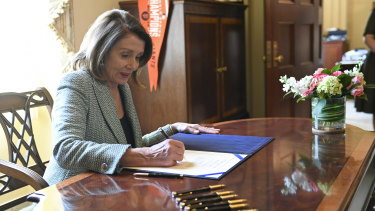 House Speaker Nancy Pelosi signs the disapproval resolution that had blocked Trump's national emergency declaration.
