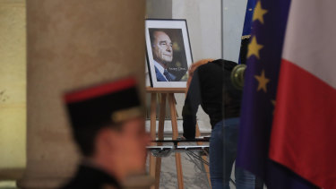 A woman signs a condolences book to pay tribute to former French president Jacques Chirac at the Elysee Palace in Paris.