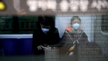 Commuters on the subway in Seoul, South Korea, wear masks to prevent the spread of coronavirus.