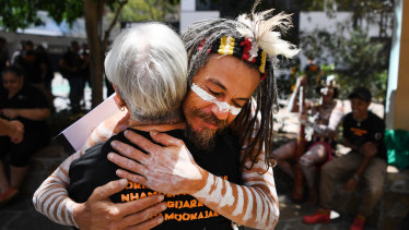 Traditional owner Joshua Walker hugs a supporter outside the Federal Court in Brisbane.