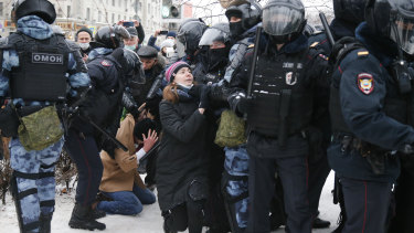 Police detain a man as another policeman stops a young woman, center, during a protest against the jailing of opposition leader Alexei Navalny in Moscow, Russia.