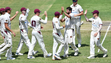 Michael Neser (centre) of the Bulls celebrates with team mates after getting the wicket of Tim Paine.