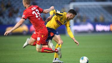 Jordan Murray of the Mariners is tackled by Adelaide United's Jordan Elsey.