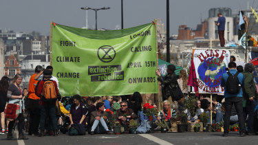 Protesters sit on the road of the blocked Waterloo Bridge in London on Wednesday. The group Extinction Rebellion is calling for a week of civil disobedience against what it says is the failure to tackle the causes of climate change.