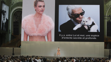 "Model Cara Delevingne is seen on a giant screen as she speaks to the invited guests during ""Karl for Ever"" at the Grand Palais in Paris, France, on Thursday, June 20, 2019."