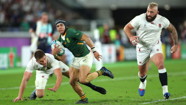 Cheslin Kolbe breaks through the tackle of Owen Farrell of England to score.