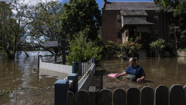 Windsor residents wading through their flooded property last week.