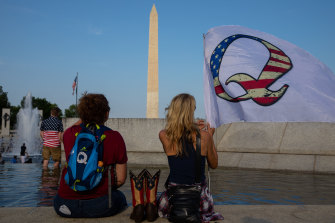 QAnon supporters wait for a military flyover at the World War II Memorial during 2020 Fourth of July celebrations in Washington.
