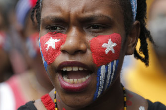 A Papuan student with her face painted with the colours of the separatist 'Morning Star' flag shouts slogans during a rally near the presidential palace in Jakarta, Indonesia, on August 29.