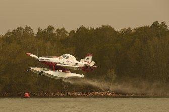 A seaplane loads water in the Moruya River to tackle fires to the north of Moruya on the NSW South Coast.