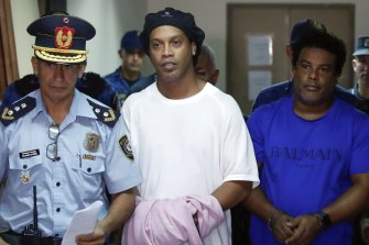 Former soccer star Ronaldinho, second from left, and his brother Roberto de Assis Moreira walks escorted by police officers to declare to judge Clara Ruiz Diaz at Justice Palace in Asuncion, Paraguay.