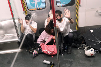 Police shoot pepper spray at protesters inside a train at Prince Edward Station, in Hong Kong.