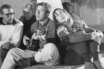 Leonard Cohen playing his guitar in  Greece with Charmian Clift, pictured in 1960.