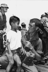 Mohammed Majivi, 8, has a sunny farewell smile for Private Peter Harding, of Oakleigh, Victoria, before the 4th Battalion left Borneo.