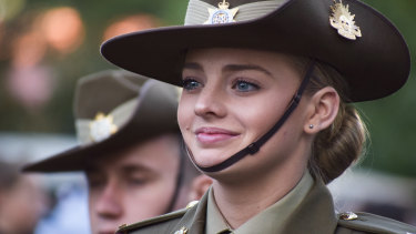 A proud servicewomen smiles to the audience as she marches down the street.