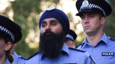 Police officer Jasvir Minhas marches down St Georges Terrace in company of fellow officers.