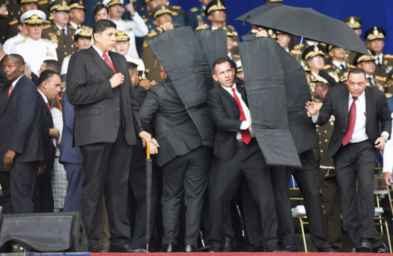 Security personnel surround Venezuela's President Nicolas Maduro in Caracas on Saturday after drones armed with explosives detonated as he gave a speech.